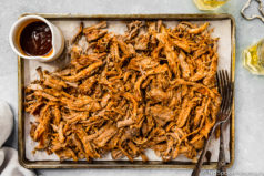Overhead, landscape shot of Easy Carolina BBQ Pulled Pork on a small sheet pan with a ramekin of BBQ sauce and two forks; with two glasses of beer and a bottle cap opener off to the side of the pan.