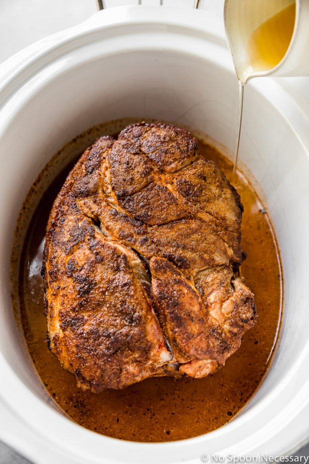 Angled shot of a seared pork butt in a slow cooker with a small container of apple cider being poured into the slow cooker. (A photo of step 3 in the recipe to make Slow Cooker Easy Carolina BBQ Pulled Pork)