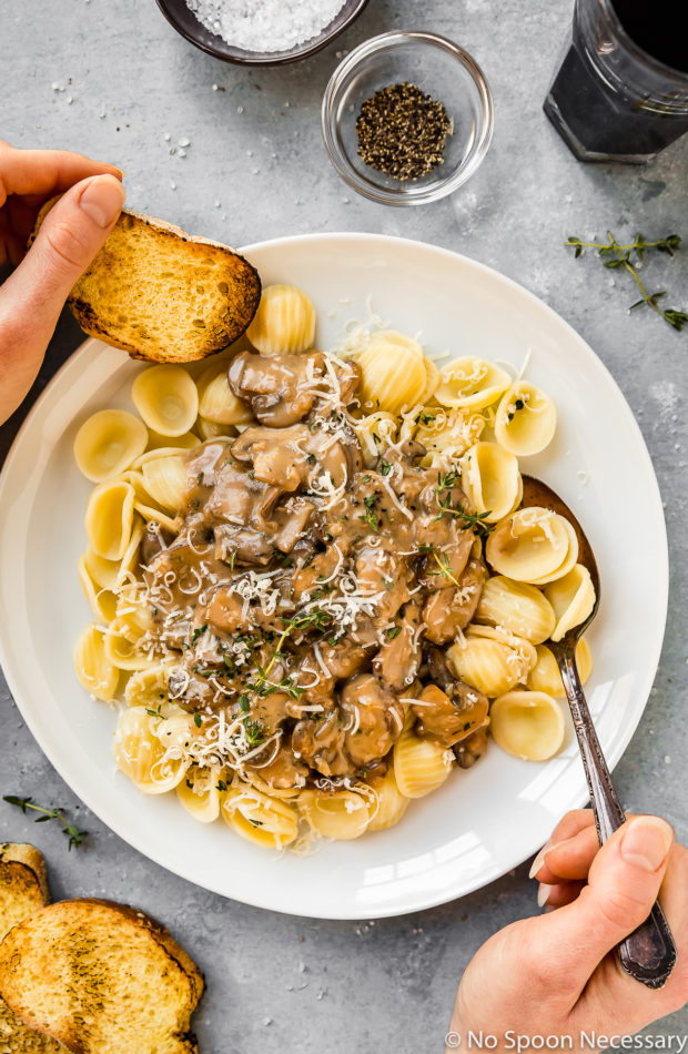 Overhead shot of white plate filled with pasta and topped with Easy Mushroom Marsala Cream Sauce with a hands holding a spoon and toasted slice of bread digging into the pasta with slices of toasted bread, red wine glasses and ramekin of salt and pepper surrounding the plate.