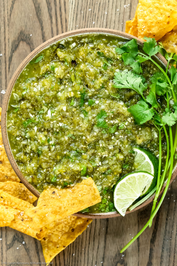Overhead photo of Homemade Salsa Verde topped with lime wedges and fresh cilantro in a neutral colored with yellow tortilla chips scattered around the bowl.