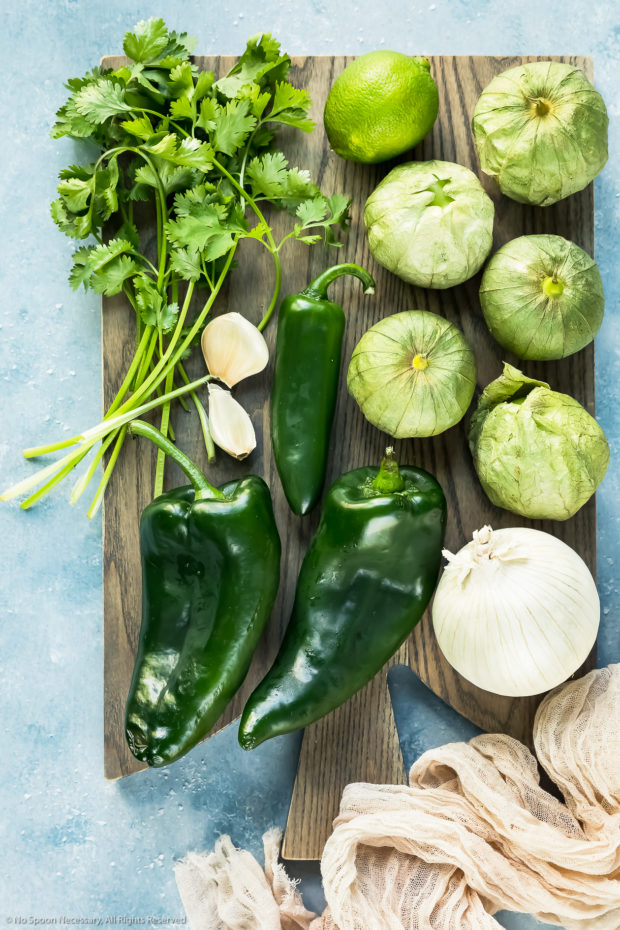 Overhead photo of all the ingredients needed to make Green Salsa on a gray wood board.