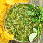 Overhead photo of Homemade Salsa Verde topped with lime wedges and fresh cilantro in a neutral colored with yellow tortilla chips scattered around the bowl and a chip inserted into the salsa.