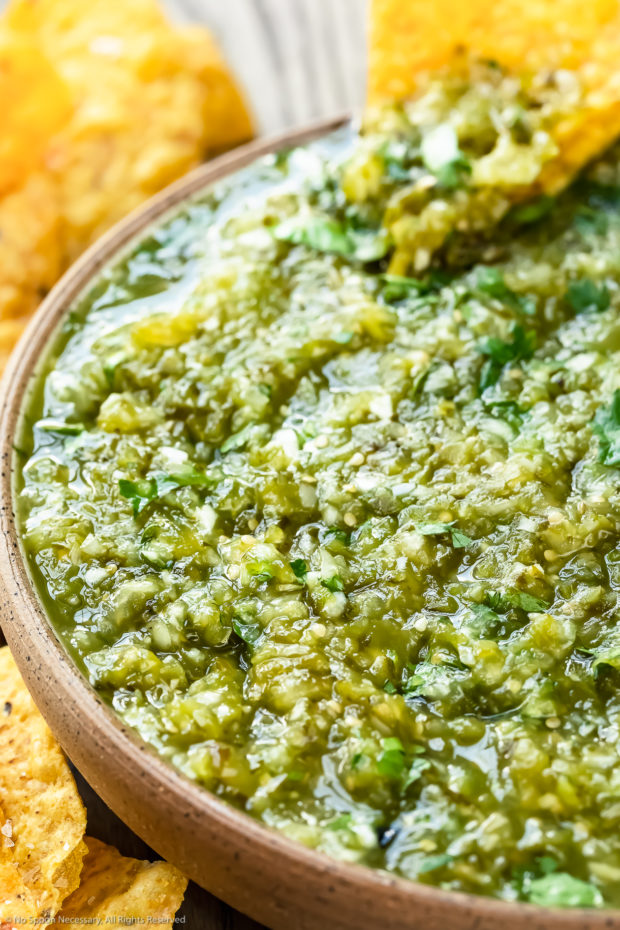 Angled, up-close photo of Green Salsa in a neutral colored with a yellow tortilla chip dipped into the salsa.