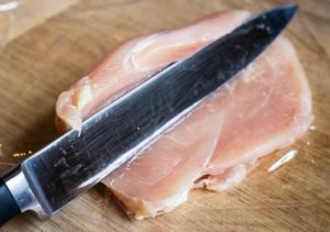 Angled shot of a knife slicing open a chicken breast for stuffing for a chicken roulade.