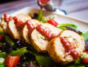45 degree angle, side shot of a Chicken Roulade stuffed with Gorgonzola, Bacon & Caramelized Onions and drizzled with a Strawberry Balsamic Reduction on a plate of mixed greens.