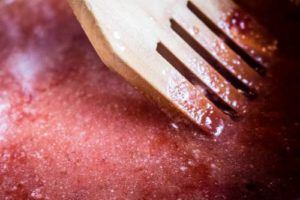 Up-close, angled shot of 45 degree angle shot of Strawberry Balsamic Reduction being cooked in a skillet.