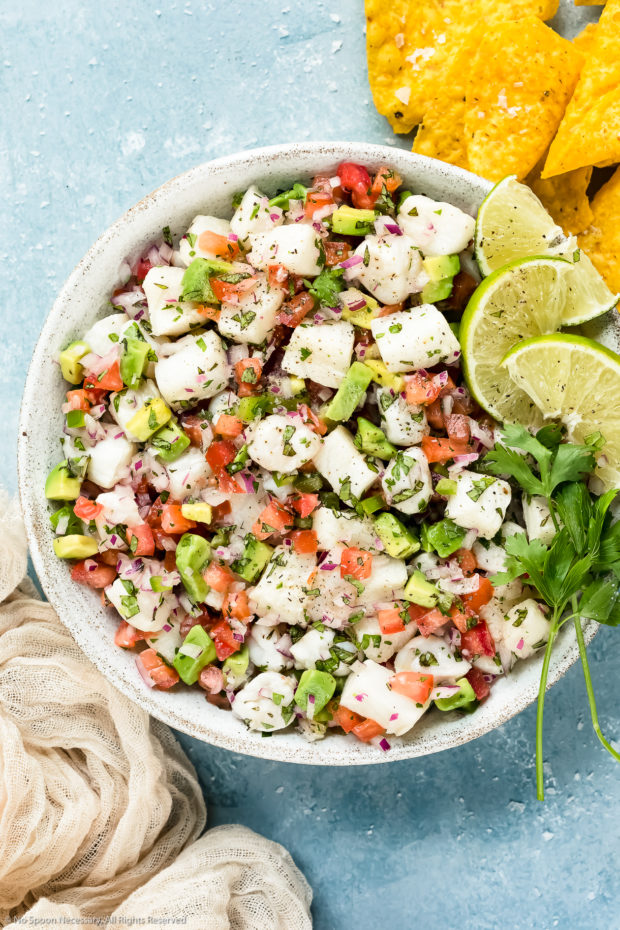 Overhead photo of Classic Fish Ceviche garnished with lime wedges and fresh cilantro in a white bowl with tortilla chips and a pale tan linen next to the bowl.
