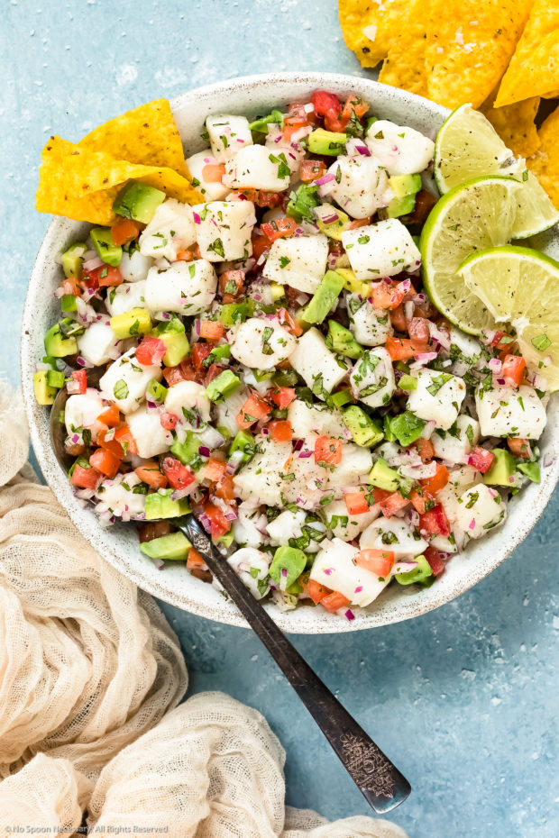 Overhead photo of Classic Fish Ceviche garnished with lime wedges in a white bowl with a serving spoon inserted into the ceviche and tortilla chips next to the bowl - photo of how to serve fish ceviche.