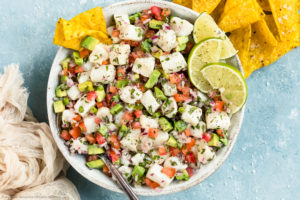 Overhead photo of Classic Fish Ceviche garnished with lime wedges in a white bowl with a serving spoon inserted into the ceviche and tortilla chips next to the bowl.
