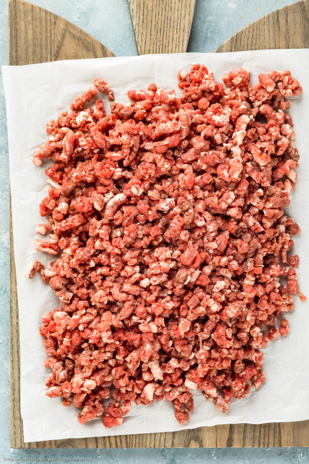 Overhead photo of homemade ground beef on a parchment paper lined wood board.