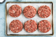 Overhead, landscape shot of homemade burger patties on a parchment paper lined sheet pan.