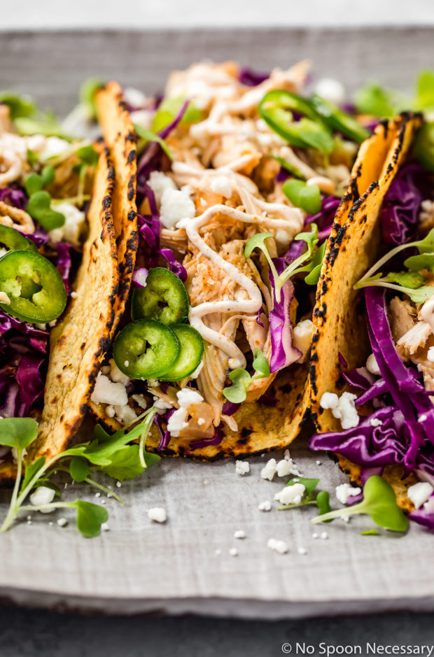 Angled, upclose shot of Slow Cooker Beer Braised Baja Chicken Tacos on a gray platter with cotija cheese and micro greens.