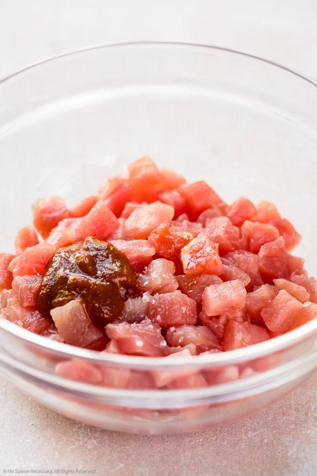 Angled photo of diced sashimi-grade tuna, chili oil, sriracha and sea salt in a glass bowl - photo of completed step 1 of the spicy tuna recipe.