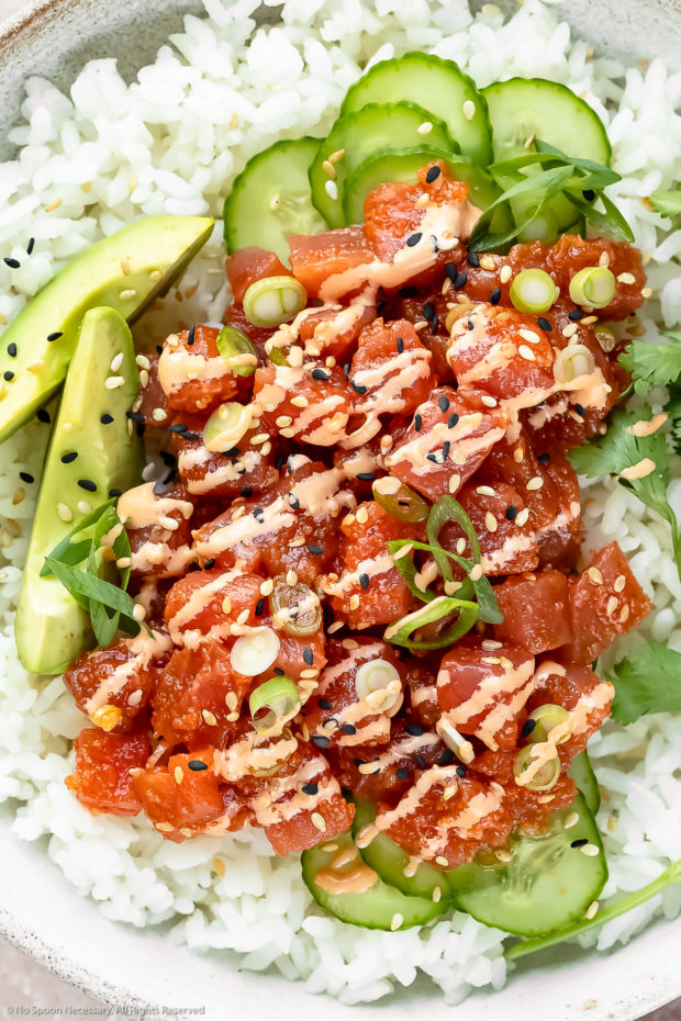 Overhead, close-up photo of Homemade Spicy Tuna Sushi Bowl drizzled with spicy mayonnaise and garnished with slices of avocado, cucumber, scallions and fresh cilantro.