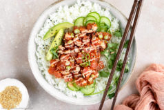 Overhead photo of Homemade Spicy Tuna Sushi Bowl garnished with spicy mayo, slices of avocado, cucumber, scallions and fresh cilantro with a pair of wooden chopsticks resting on the bowl and a ramekin of sesame seeds and pink linen arranged around the bowl.