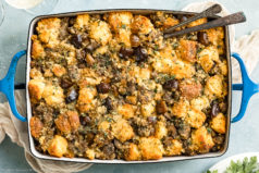 Overhead photo of baked Roasted Chestnut Stuffing in a blue baking dish with serving spoons inserted into the stuffing and glasses of wine and a pale neutral color linen next to the dish.