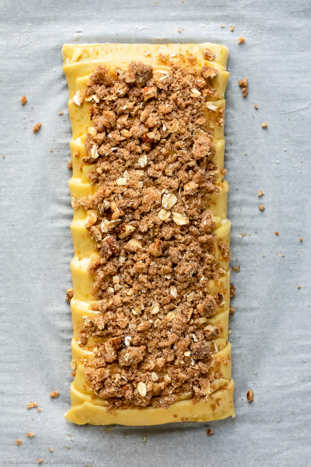 Overhead photo of a homemade cheese pastry braid topped with streusel before being baked.