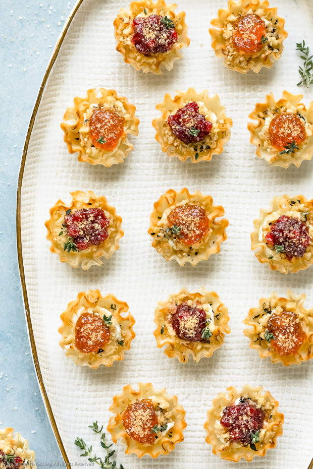 Overhead photo of Goat Cheese Phyllo Cup Appetizers topped with jam on a white platter.