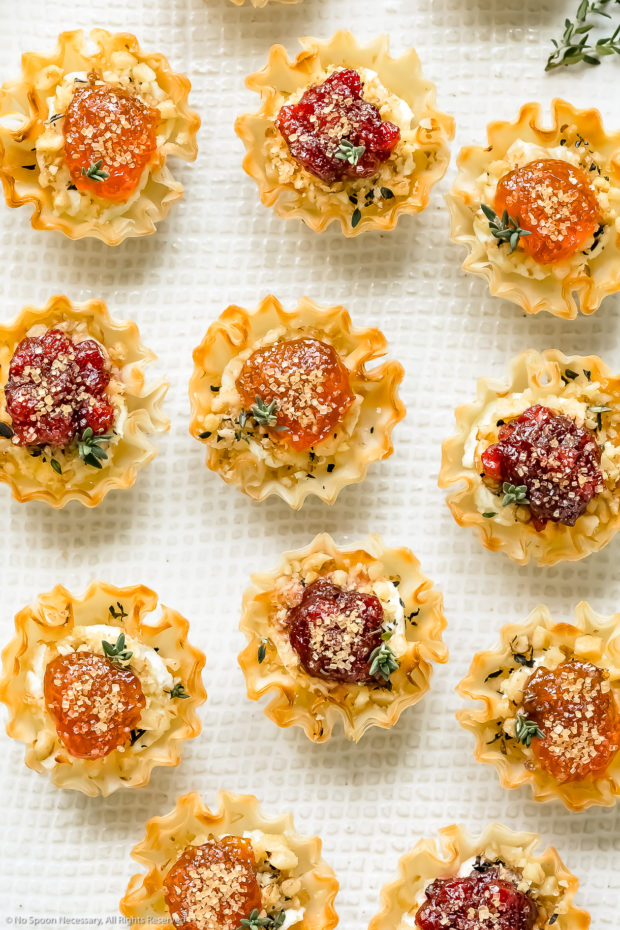 Overhead, up close photo of Goat Cheese Phyllo Cup Appetizers topped with jam and fresh thyme on a white platter.