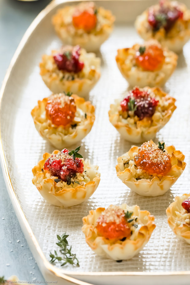 Angled photo of Goat Cheese Phyllo Cup Appetizers garnished with fresh thyme on a white platter.