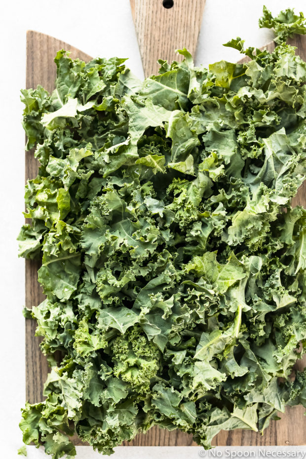Overhead shot of cleaned, washed and chopped kale on a gray cutting board - photo of the prep for Warm Kale Salad recipe.