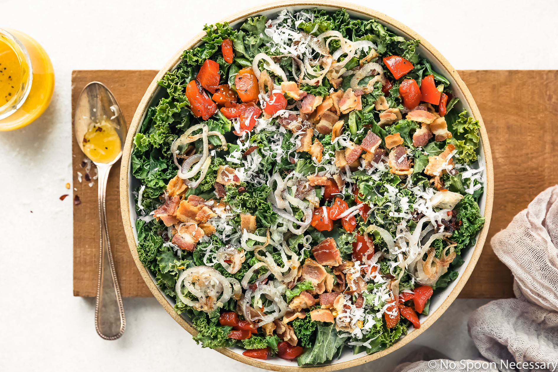 Overhead, landscape shot of Warm Kale Salad topped with bacon, shallots, roasted red peppers and shredded parmesan cheese in a large serving bowl with a small jar of Honey Dijon Vinaigrette, ramekin of crushed pepper flakes and a pale purple linen arranged around the bowl.