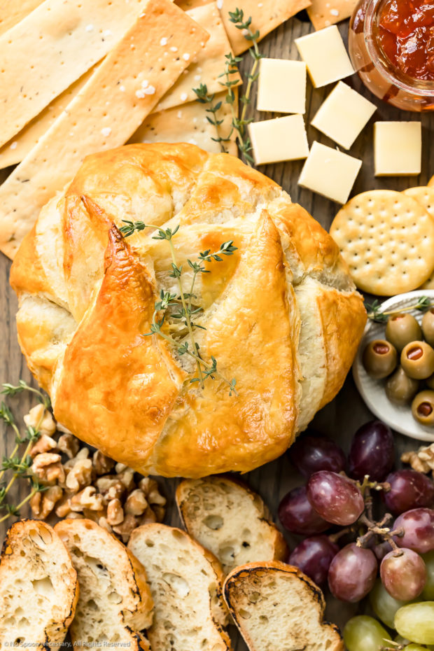 Overhead photo of freshly baked brie en croute garnished with fresh thyme leaves on a cheeseboard with crackers, slices of bread, grapes, olives and nuts.