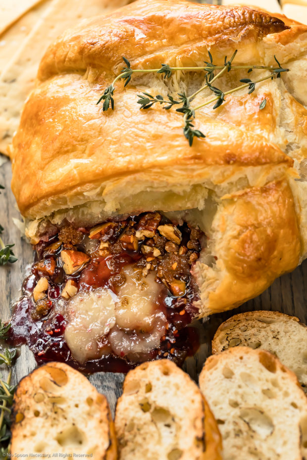 Angled, up close photo of Baked Brie en Croute that has been cut into to showcase the oozing cheese, jam and nuts.