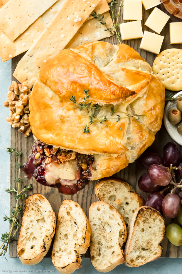 Overhead photo of Baked Brie en Croute that has been cut into on a large cheese board surrounded by crackers, slices of bread, olives, jam, grapes and nuts.