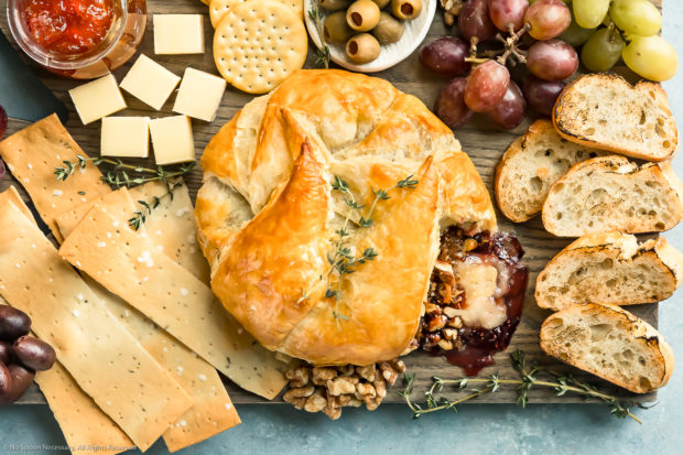 Overhead photo of Baked Brie en Croute on a large cheese board surrounded by crackers, slices of bread, olives, jam, grapes and nuts.