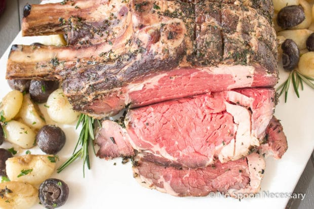 Overhead shot of a partially carved Herb Crusted Standing Rib Roast on a large white platter with roasted mushrooms and onions.