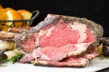 Straight on shot of a Herb Crusted Standing Rib Roast on a large white platter with roasted mushrooms and onions.