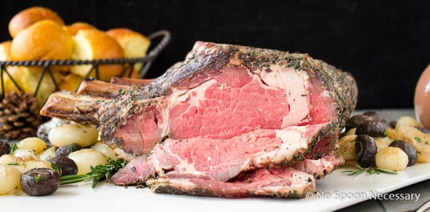 Straight on shot of a partially carved Herb Crusted Standing Rib Roast on a large white platter with roasted mushrooms and onions and a basket of dinner rolls blurred in the background.