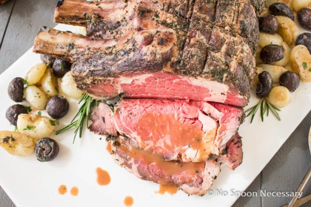 Overhead shot of a partially carved Herb Crusted Standing Rib Roast drizzled with horseradish gravy on a large white platter with roasted mushrooms and onions.