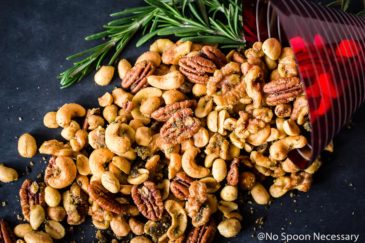 Overhead, landscape shot of Savory & Spicy Rosemary Roasted Mixed Nuts spilling out of a red martini glass with fresh rosemary on a black chalk colored board.