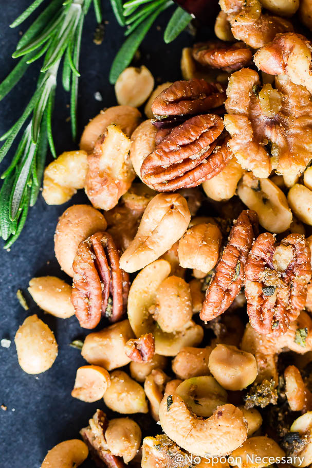 Close-up Overhead shot of Savory & Spicy Roasted Rosemary Mixed Nuts with fresh rosemary on a black chalk colored board.