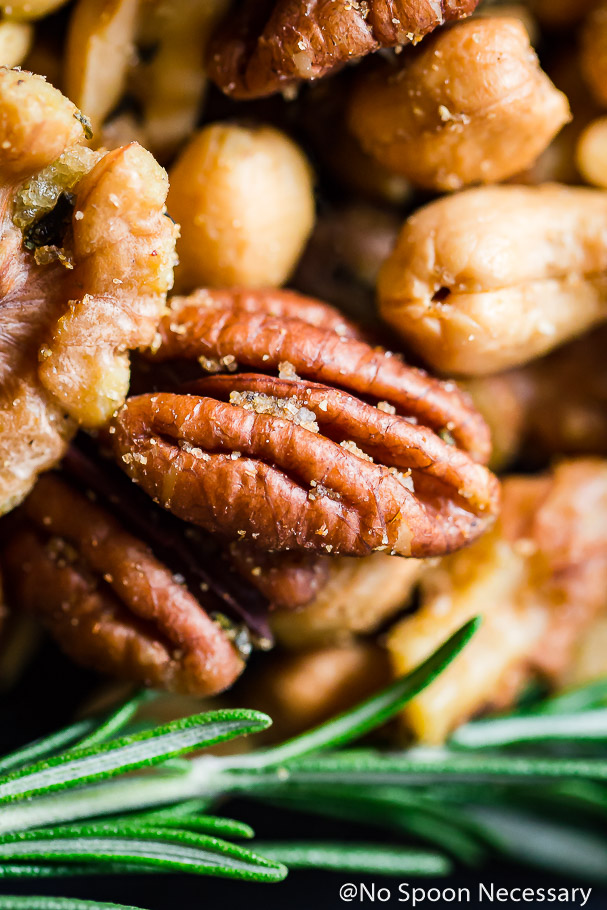 Extreme close-up, over head shot of Overhead shot of Savory & Spicy Rosemary Roasted Mixed Nuts with a sprig of fresh rosemary.
