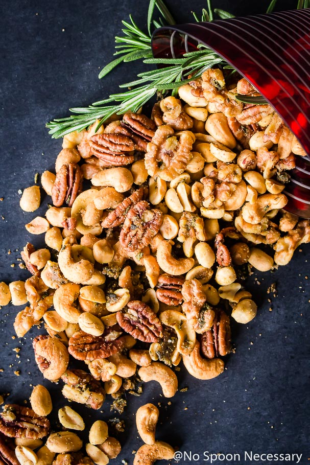 Overhead shot of a Rosemary Roasted Mixed Nuts pouring out of a red and white stripped martini glass with fresh rosemary on the side.