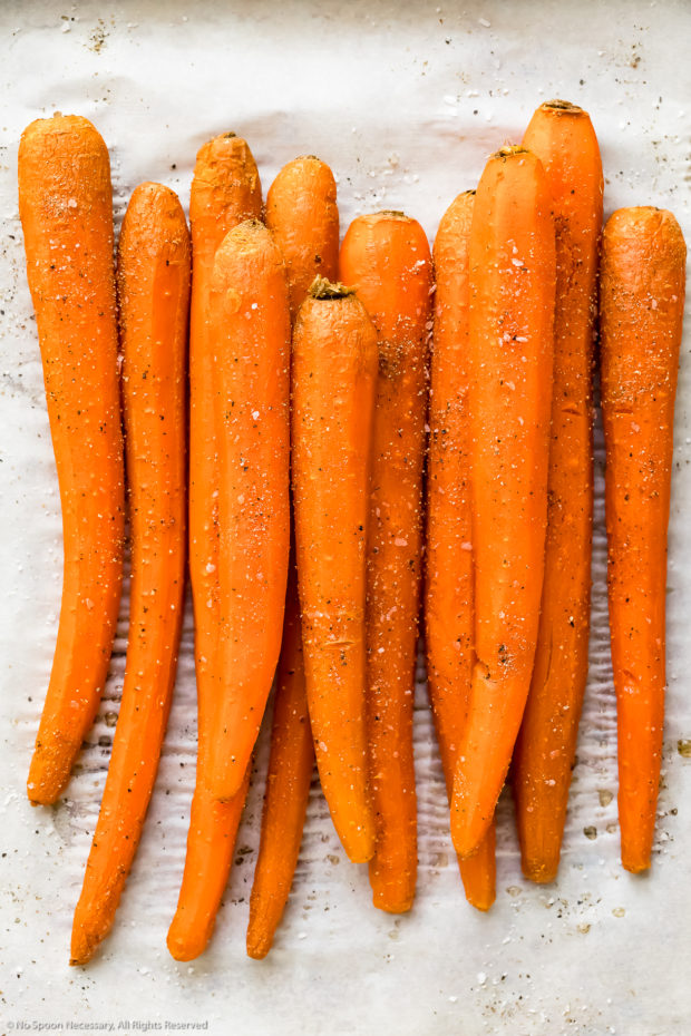 Overhead photo of roasted carrots seasoned with salt and pepper on a parchment paper lined sheet pan - photo of cooked carrots to make dip.