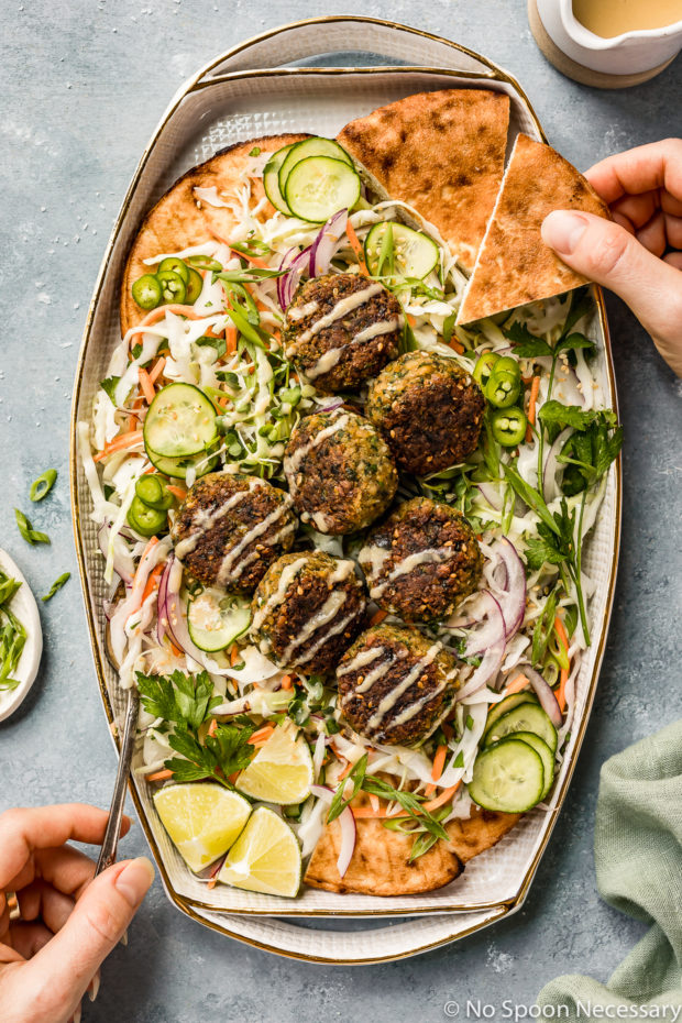 Overhead shot of a platter of Asian Crispy Pan Fried Falafels on a bed of Asian slaw with a hand holding a piece of pita bread and another hand holding a spoon inserted into the slaw.