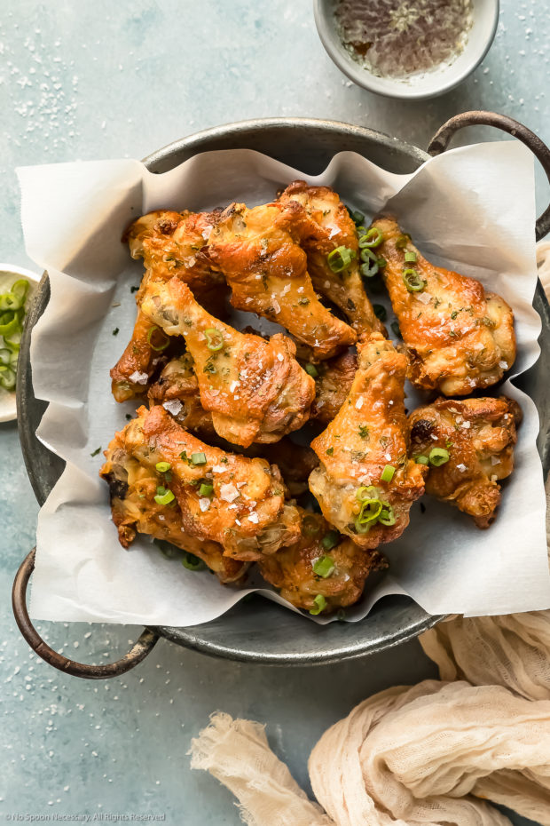 Overhead photo of Salt & Vinegar Chicken Wings in a metal serving bowl lined with parchment paper with ramekins of dipping sauce and sliced scallions arranged around the bowl.