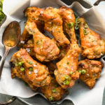 Overhead, landscape photo of Salt & Vinegar Chicken Wings in a metal serving bowl lined with parchment paper with ramekins of dipping sauce and sliced scallions arranged around the bowl.