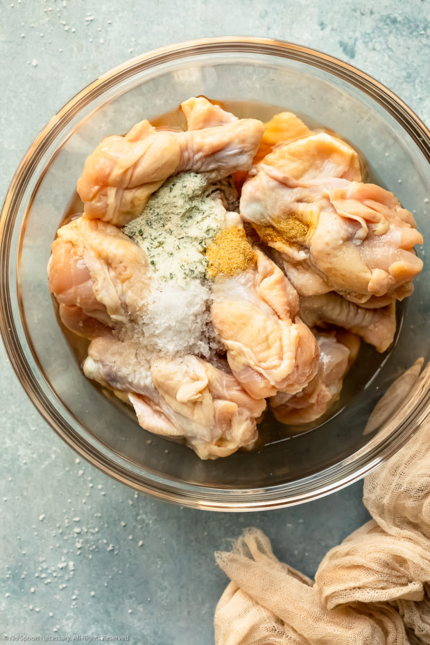 Overhead photo of raw chicken wings topped with the ingredients for salt and pepper marinade in a glass bowl - photo of step 2 of the recipe.