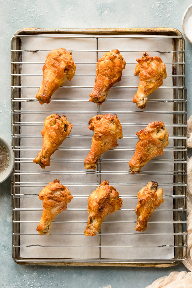 Overhead photo of baked salt and vinegar chicken wings on a wire rack lined sheet pan - photo of step 6 of the recipe.
