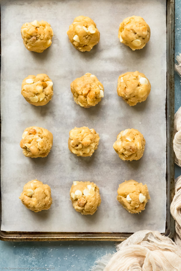 Overhead photo of white chocolate macadamia nut cookie dough rolled into individual balls on a parchment paper lined cookie sheet.
