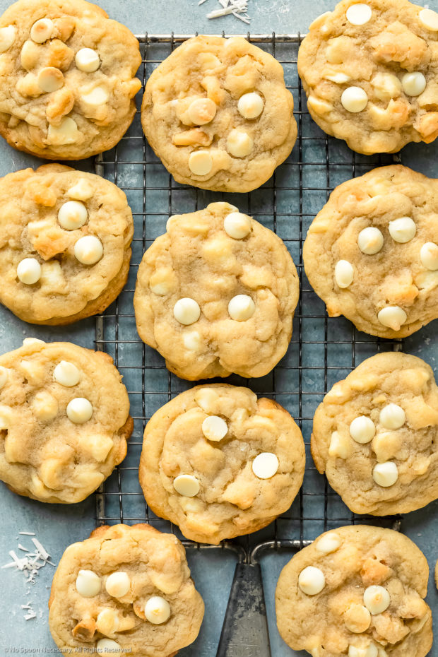 Overhead photo of White Chocolate Macadamia Nut Cookies scattered out on a wire rack on a blue surface.