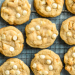 Overhead, landscape photo of White Chocolate Macadamia Nut Cookies scattered out on a wire rack on a blue surface.