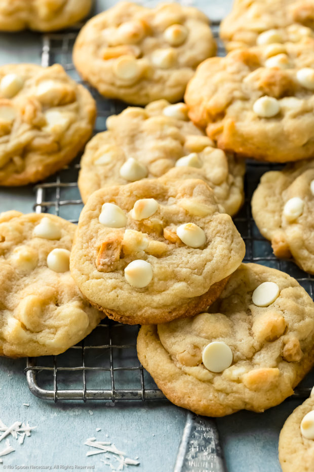 Angled photo of White Chocolate Macadamia Nut Cookies scattered on top of each other on a wire rack on a blue surface.