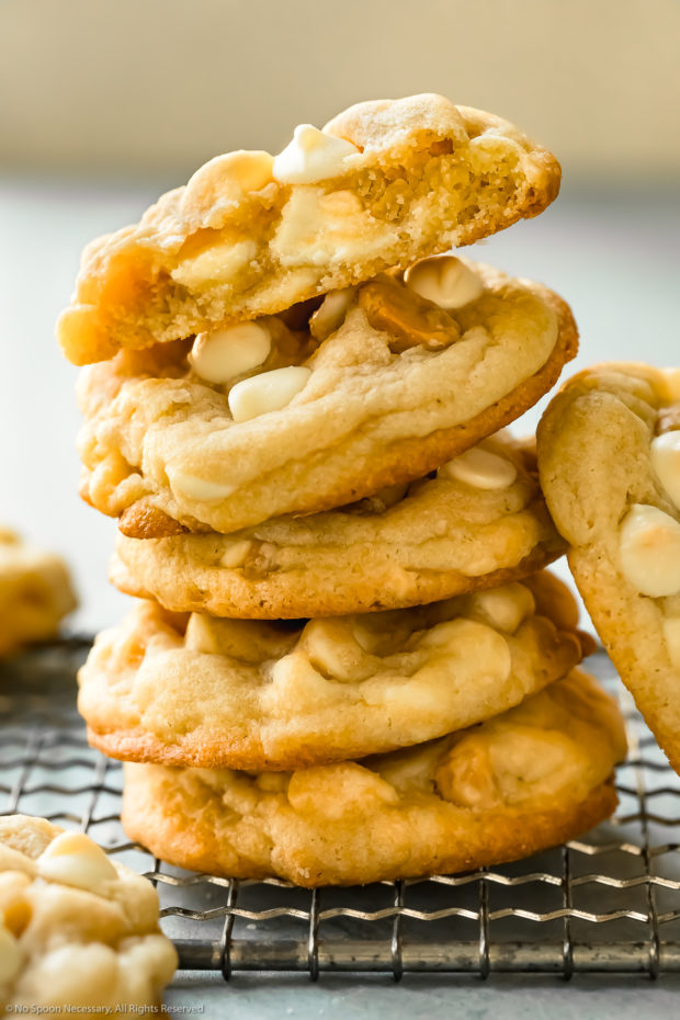 Straight on shot of a stack of white chocolate macadamia nut cookies on a wire rack with the top cookie torn in half to show the soft and chewy interior.