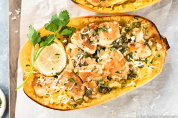 Overhead shot of Healthy Chicken Piccata Spaghetti Squash Boats garnished with a slice of lemon and sprig of fresh parsley on a parchment paper lined wood serving board with a ramekin of chopped parsley next to the board.